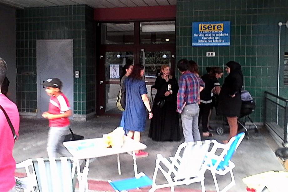 Devant le Service local de solidarité, jeudi 29 juin, les parents d'élèves qui n'ont pas été autorisés à rentrer attendent l'issue de la réunion. (photo : BB, Le Crieur de la Villeneuve)